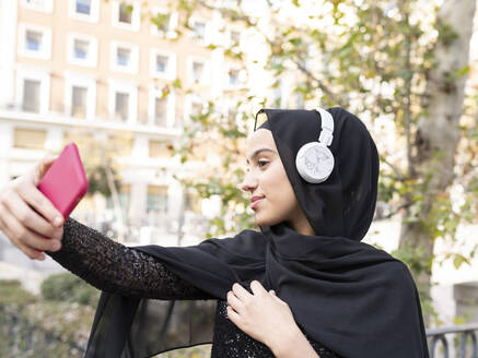 Portrait of young beautiful woman wearing hijab and headphones taking smart phone selfie - JCCMF00469