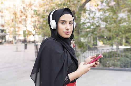 Portrait of young beautiful woman wearinghijaband headphones using smart phone - JCCMF00472