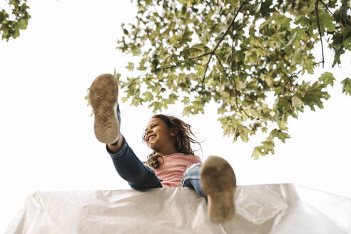 Low angle view of smiling girl sitting on table against clear sky during summer - MASF21125