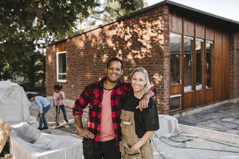 Portrait of confident couple standing while children playing in background against house - MASF21146