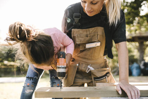 Daughter using drill machine on wooden plank by mother in yard - MASF21149
