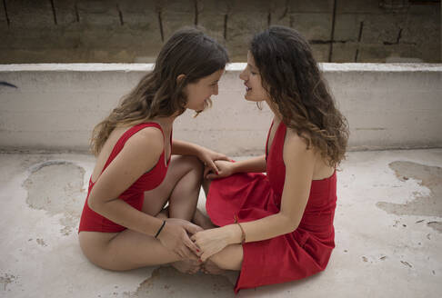 Sisters wearing red clothing with face to face sitting on terrace - AXHF00005