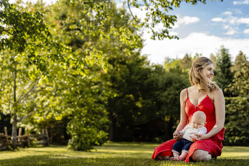Smiling mother holding baby boy while kneeling on grassy land in park - AWAF00024
