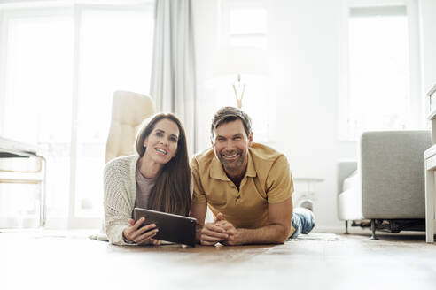 Smiling mature man and woman with digital tablet lying on floor in apartment - JOSEF02757