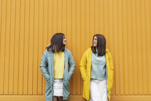 Sisters wearing yellow and blue raincoats smiling while looking at each other standing against wall - AXHF00011