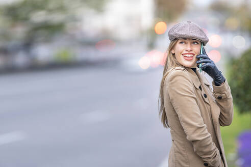 Smiling attractive woman talking on smart phone standing on street - GGGF00704