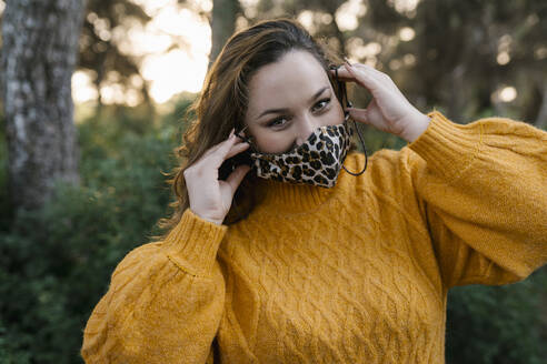 Young woman wearing protective face mask while standing at forest - EGAF01350