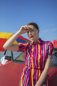 Beautiful woman standing by car at beach on sunny day - AXHF00020