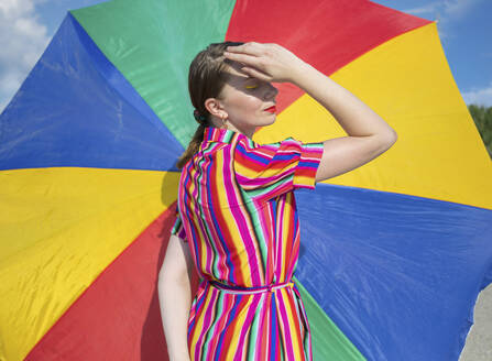Mid adult woman by colorful beach umbrella on sunny day - AXHF00023