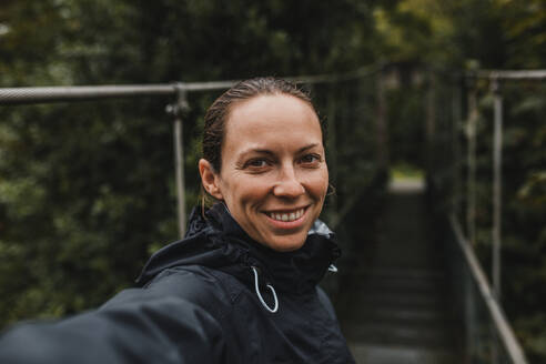 Smiling mid adult woman on suspension bridge during rainy day - DMGF00423