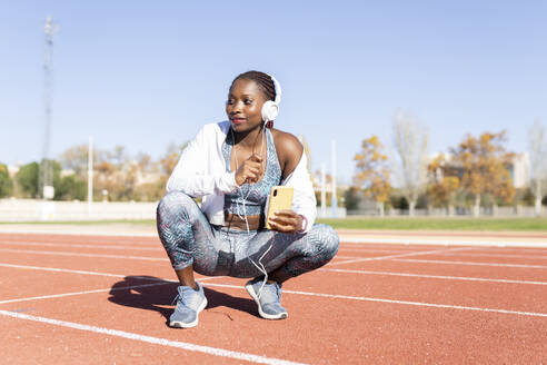Female sportsperson with mobile phone listening music while crouching on sports track during sunny day - JCCMF00516