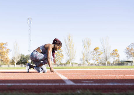 Female sportsperson in starting position on sports track during sunny day - JCCMF00525