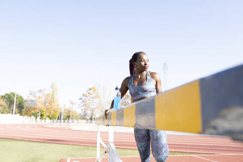 Female sportsperson looking away while exercising by balance beam against clear sky - JCCMF00537
