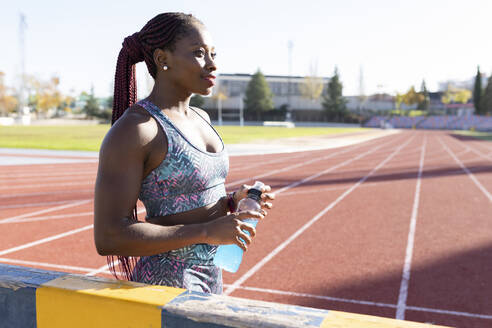 Thoughtful female sportsperson holding energy drink bottle on sports track during sunny day - JCCMF00540