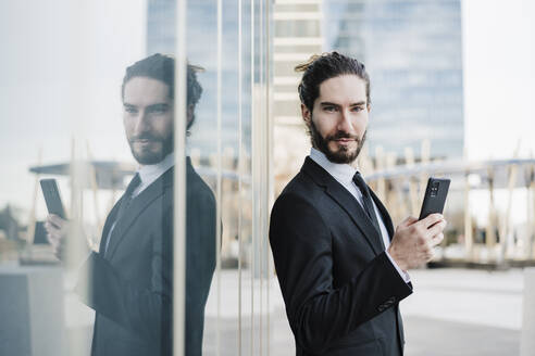 Entrepreneur using mobile phone while standing by glass wall - EBBF02013