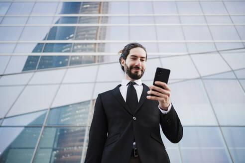 Smiling entrepreneur using smart phone while standing against building - EBBF02034