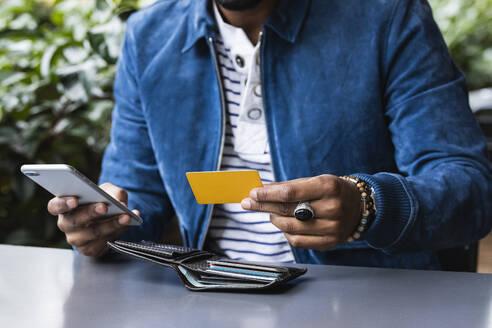 Close-up of man with credit card making mobile payment at sidewalk cafe - PNAF00493