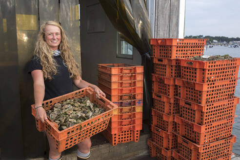 Female shellfish farmer holding crate of oysters - CAVF91485