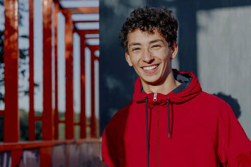 Smiling young man wearing red hood standing against wall during sunny day - OGF00754