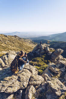 Young woman photographing male friend sitting on mountain against clear sky - RSGF00481