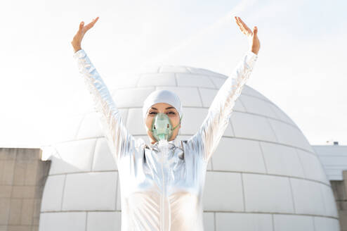 Young woman wearing protective suit and oxygen mask standing with hand raised against igloo - JCCMF00564