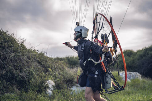 Young man, with the Powered Paragliding engine in his shoulders, runs on the lawn, and gets ready to jump and fly. - CAVF91504