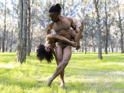 Two professional dancers performing in underwear in middle of forest - JCCMF00594