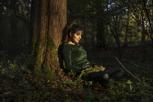 Mid adult woman leaning on tree trunk in sunlight during autumn - AXHF00030