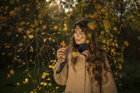Beautiful woman wearing warm jacket looking at autumn leaf in park - AXHF00042