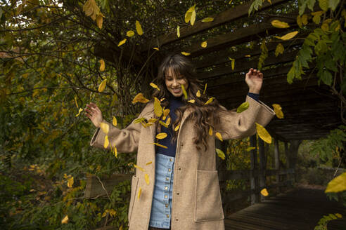 Happy woman with arms raised standing in falling leafs at public park during autumn - AXHF00045