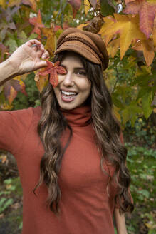 Cheerful woman in cap covering eye while standing in autumn park - AXHF00048