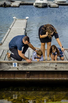 Family looking at water from pier - AWAF00028