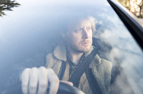 Close-up of thoughtful man sitting in car seen through windshield - JCCMF00631