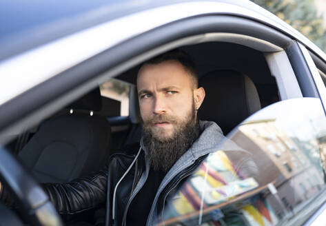 Bearded man looking away while driving car seen through window - JCCMF00634