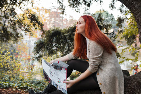 Beautiful woman with brown hair holding map while sitting in park - MRRF00776