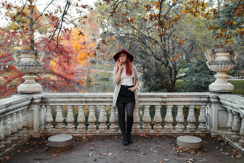 Thoughtful beautiful woman wearing hat while leaning on railing against lake - MRRF00782