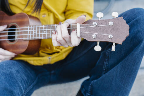 Close-up of woman playing guitar while sitting outdoors - JCZF00433
