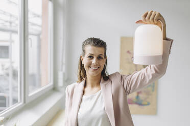 Portrait of smiling businesswoman holding lantern in office - GUSF04997