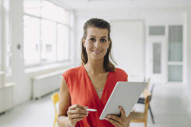 Portrait of businesswoman with digital tablet standing in office - GUSF05018