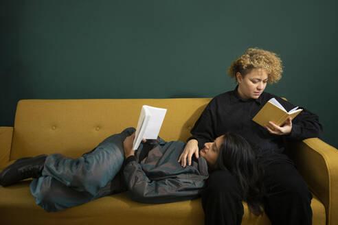Lesbian couple reading books on sofa - AXHF00067