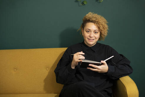 Portrait of young woman sitting on sofa with note pad in hands - AXHF00070