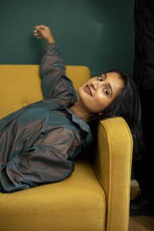 Portrait of young brunette lying on yellow sofa - AXHF00073