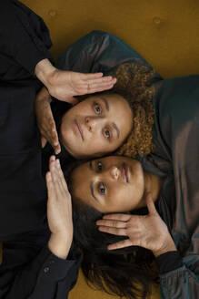 Portrait of lesbian couple lying together on sofa - AXHF00082
