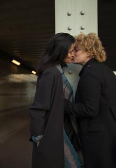 Lesbian couple kissing under bridge at night - AXHF00091