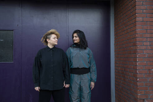 Lesbian couple holding hands in front of building entrance - AXHF00094