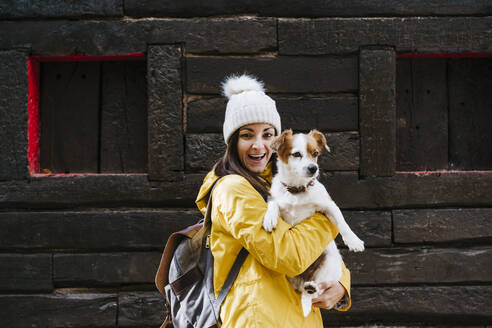 Portrait of smiling woman in yellow raincoat holding dog in front of log cabin - EBBF02098