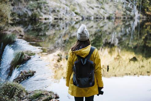Woman in yellow raincoat facing river and waterfall - EBBF02110