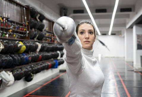 Womanin fencing outfit practicing at gym - JCCMF00716