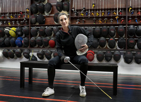 Portrait of womanin fencing outfit sitting at gym - JCCMF00731