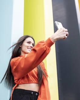 Portrait of beautiful brunettetalking smart phone selfie - JCCMF00779